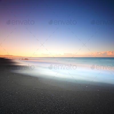 Beach dark sand and sea on morning. Tuscany Italy