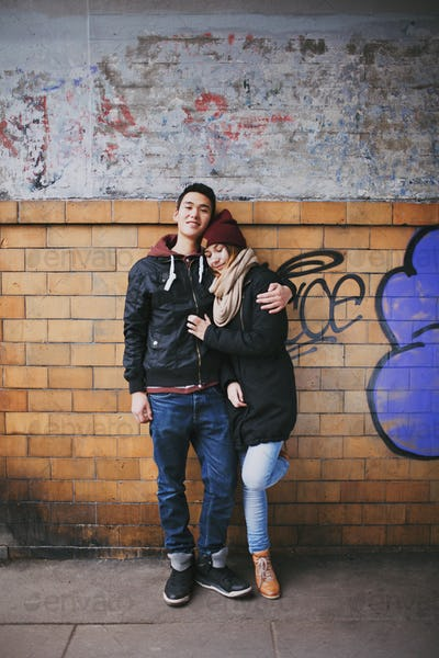 Affectionate couple embracing against a wall