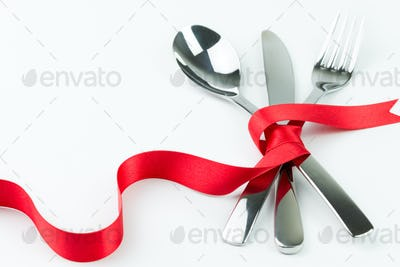 Fork, spoon and knife tied up with red ribbon
