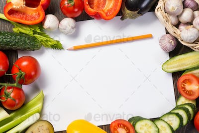 Vegetables tiled around a sheet of paper
