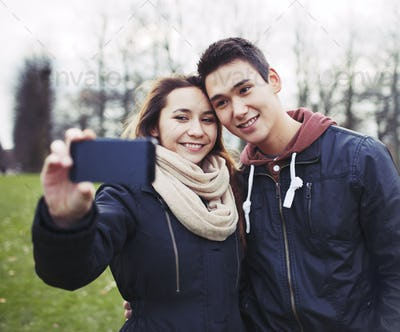Cute young couple taking self portrait with smartphone in park