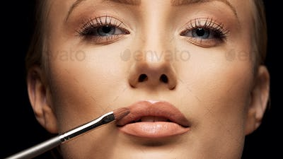 Close up crop of female face applying make up