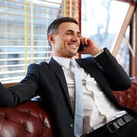 Happy businessman sitting and talking on the phone at office