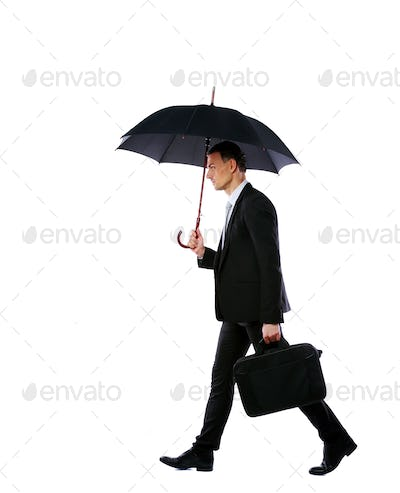 Businessman walking with umbrella and laptop bag isolated on a white background