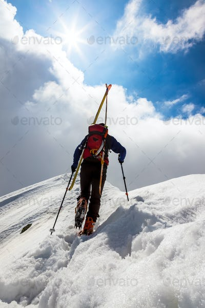 Ski mountaineer walking up along a steep snowy ridge with the skis in the backpack.