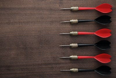 Red And Black Darts On Wooden Background