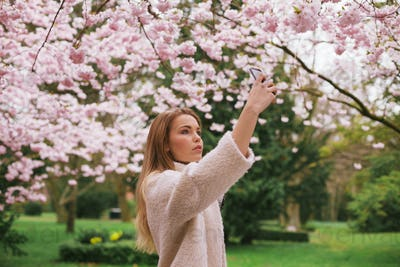 Attractive woman photographing flowers at the spring garden