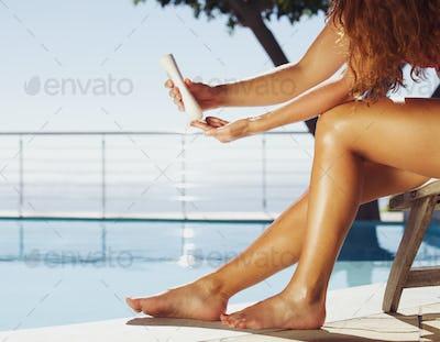 Women applying sun cream on legs