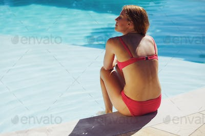 Young woman sitting on the edge of pool