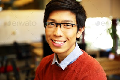 Closeup portrait of a Young happy asian man with glasses