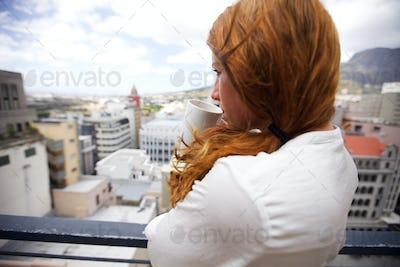 Attractive brunette drinking coffee in balcony