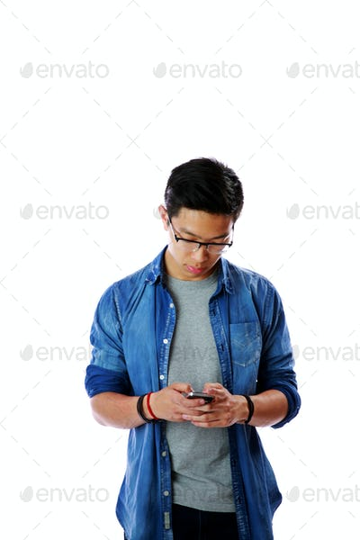 Young asian man in glasses using smartphone over white background