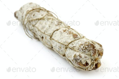 close up of a typical italian salami on white background