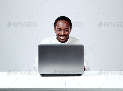 Smiling african man sitting at the table and using laptop on gray background