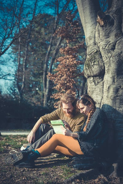 young modern stylish couple using tablet urban