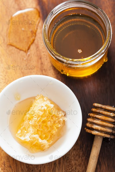 honeycomb dipper and honey in jar on wooden background