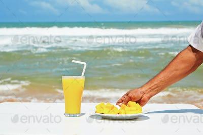 Fresh mango fruit and juice on the beach