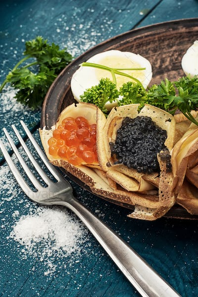 delicious pancakes stuffed with red and black caviar