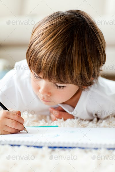 Serious little boy drawing lying on the floor