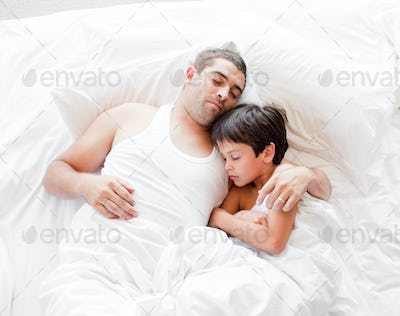 Father and Son Lying on bed and sleeping at home