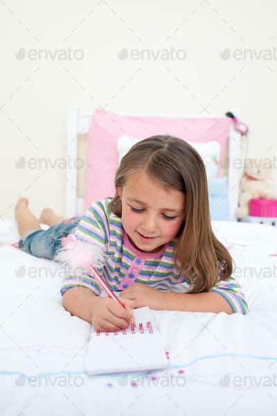 Little girl writing on a notebook