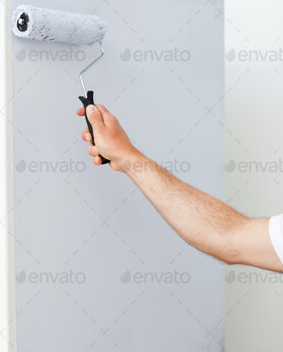 Close up of a man painting a wall in white