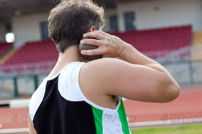 Concentrated male athlete preparing to throw weight