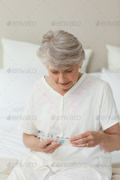 Sick senior woman taking her pills