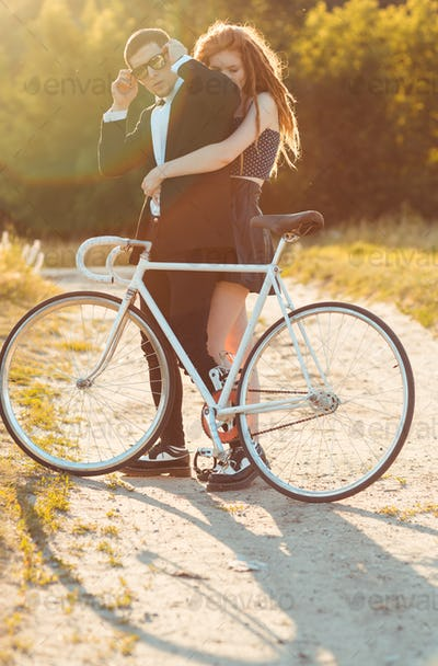 Young stylish guy with girl and the bicycle outdoors
