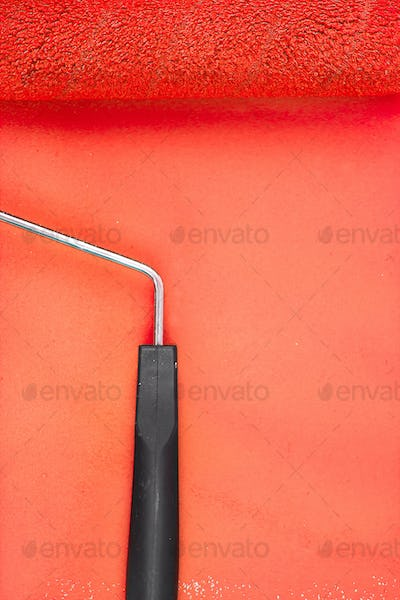 Red paint roller with handle on a background