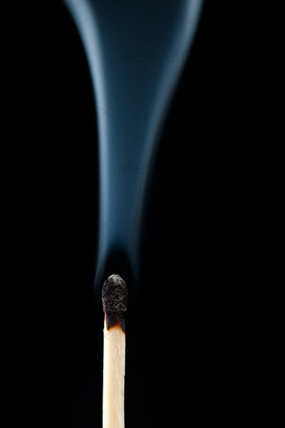Smoking consumed match against a black background