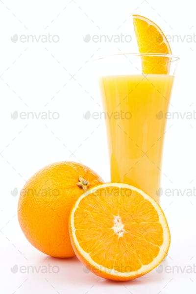 One orange and a half next to a glass of orange juice against white background