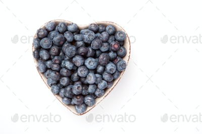 Blueberries in a heart shaped bowl against a white background