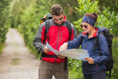 Couple going on a hike together looking at map in the countryside