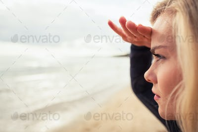 Close up side view of a beautiful blond shielding eyes at the beach