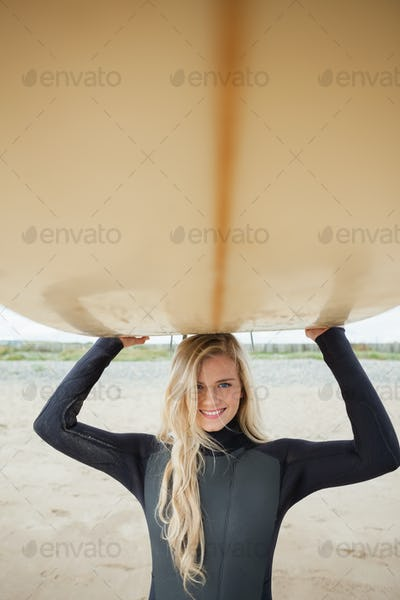 Portrait of a smiling young woman in wet suit holding surfboard over head at beach