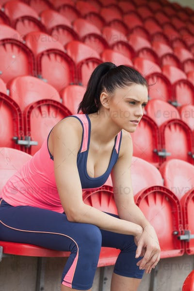 Side view of a serious toned young woman sitting on chair in the stadium