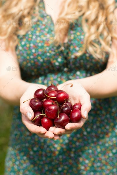 Close up of a blonde woman holding some cherries while wearing a nice dress