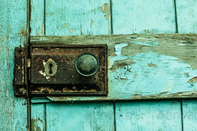 Close up of rusty lock on blue chipped rustic door