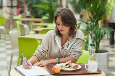 Female student doing homework while having breakfast in the cafeteria