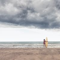 Rear view of a calm woman in bikini with surfboard on beach