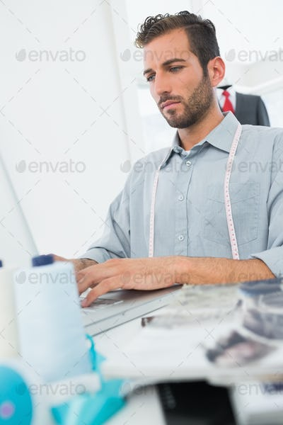 Young male fashion designer using laptop in the studio