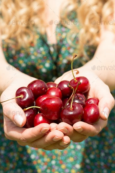 Close up of a blonde woman showing some cherries while wearing a cute dress