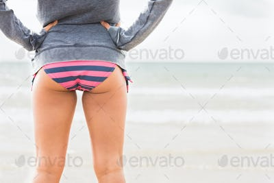 Mid section of a woman in bikini bottom and jacket at beach