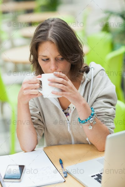 Serious female student drinking coffee while using laptop at cafeteria table